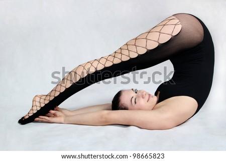 Flexible model in black stockings bending over
