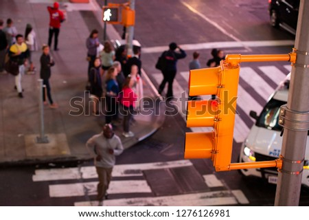 (focus on the traffic light) Close-up view of a traffic light and blurred people in the background crossing the street in Times Square, New York City, United States. stock photo