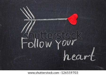 FOLLOW YOUR  HEART phrase by hand on a blackboard