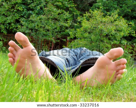 foot and a heel of the young man laying on a grass - stock photo