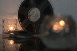 400 foot 8mm film reel in focus surrounded by blurred candles and two 50 foot 8mm reels.