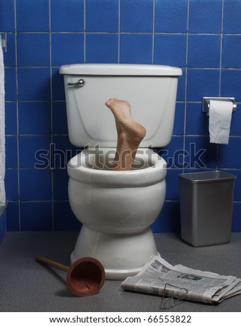 Foot reaches up through the seat from out of a toilet in a domestic bathroom.
