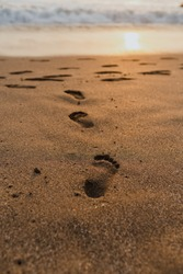 Footprints in the sand on a Balinese beach during sunset