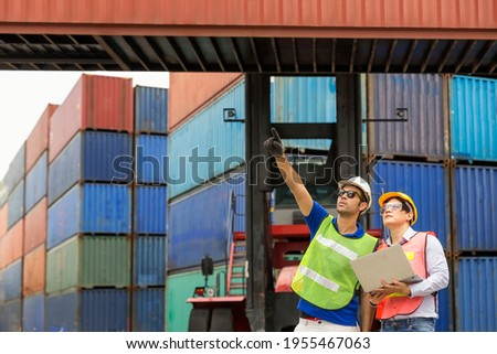 Foreman using laptop computer in the port of loading goods. Foreman control loading containers boxs from cargo freight ship for import export. Foto stock ©