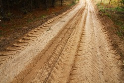 Forest road with sand. Footprints in the sand from a large truck