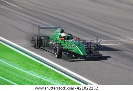Formula 2.0  race car on speed track with motion blur at sunny day