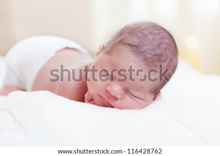fortnight newborn baby in a diaper sleeps, lying on a stomach