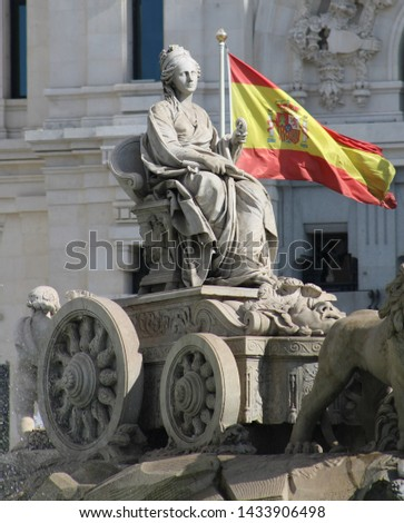 Fountain of the Goddess Cibeles in the center of Madrid, Spain, with the flag of Spain #1433906498