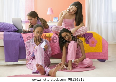 """Four girls sitting in bedroom with computer, journal, cell phone and fingernail polish """