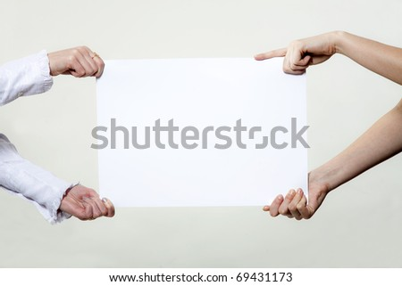 Four hands holding blank advertisement paper