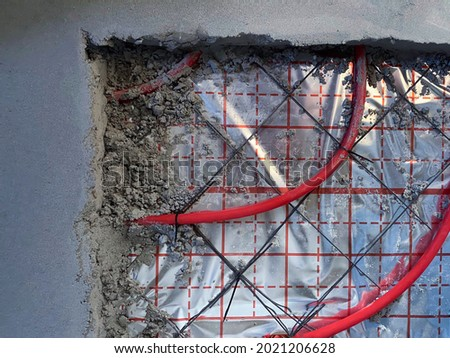 А fragment of an installed floor heating pipes and a cement screed above it. The cable is attached to the mesh, underneath there is thermal insulation Сток-фото ©