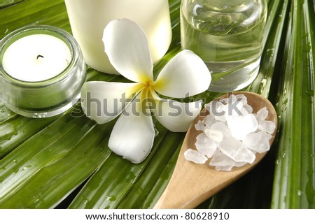 Frangipani flower and candles with massage oil and natural sea bath salt in wood bowl on palm leaf