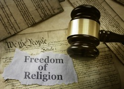 Freedom of Religion newspaper headline on a copy of the US Constitution with gavel