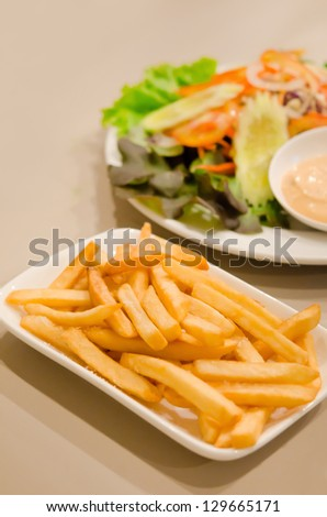 french fries on  white plate served with fresh salad