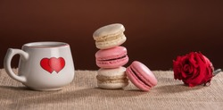 4 French pink and vanilla macarons, a red rose and one coffee cup with a red heart painted on it, placed on a beige fabric and a chocolate background
