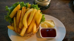 frenchfried or Potato chips placed on a cylindrical weave container. Served with tomato sauce and mayonnaise