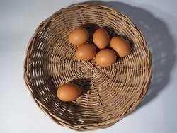 6 fresh chicken eggs in a wooden tray