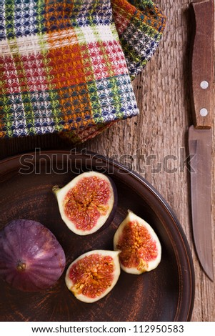fresh figs in a plate, old knife and chequered towel on rustic wooden table - stock photo