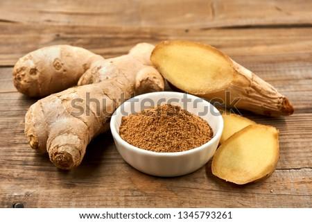 Fresh ginger on wood background,