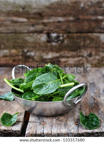 fresh green spinach in to the bowl