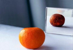 А fresh orange on the table is reflected in the mirror as rotten фтв spoiled fruit. Conceptual photo about young and old age, inner beauty, loneliness, lies.