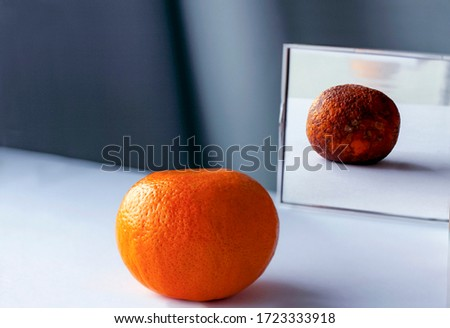 А fresh orange on the table is reflected in the mirror as rotten фтв spoiled fruit. Conceptual photo about young and old age, inner beauty, loneliness, lies. Сток-фото ©