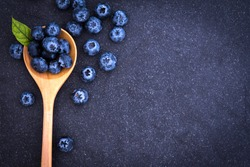 fresh picked blueberries in wooden spoon on black stone background