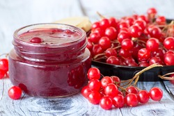 Fresh red berries of a viburnum and a glass jar with jam on a gray wooden table.