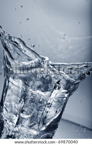 Fresh water splashing out of a glass with ice cubes  over gradient background