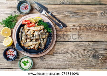 Fried sardines with lemon and salad.top view.
