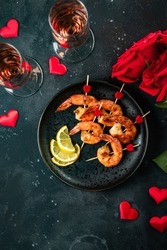 Fried shrimp, roses and champagne. Original appetizer for Valentine's Day, romantic dinner. Top view, vertical photo
