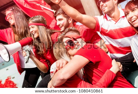Friends football supporter fans hugging each other watching soccer match event at stadium - Young people group with red t-shirts having excited fun after goal on sport world championship concept
