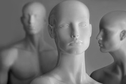 front image of shiny white female mannequin doll with a male mannequin figure in the back, on black and white background. front image of a display dummy figures