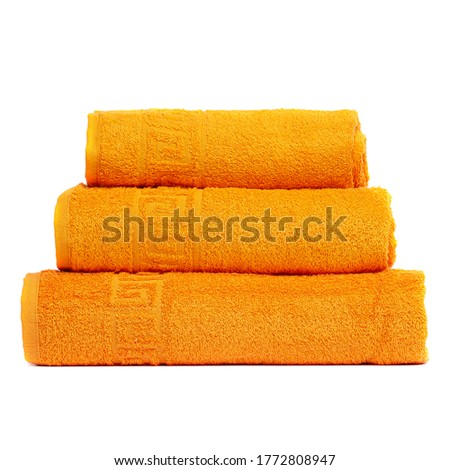3 frotte towels orange color, bedroom towel white backgroung. Colorful orange bath towels isolated on white. Stack orange towels. Pile colored towels isolate. Three cotton towel of same color stacked
