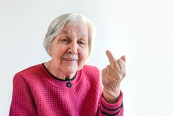 Fuck off. The gray-haired elderly lady shows the middle finger and smiles. The old woman jokingly demonstrates indecent gesture.