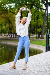 Full body portrait of a young beautiful blonde girl in white sweater and blue jeans, autumn park outdoor
