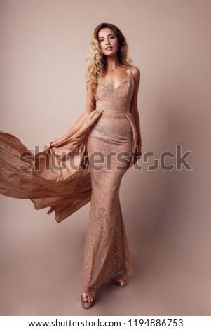 Full length  image of amazing luxury seductive woman in stylish  dress posing in studio on beige background. Bright smokey eyes make up, healthy wavy hairs.