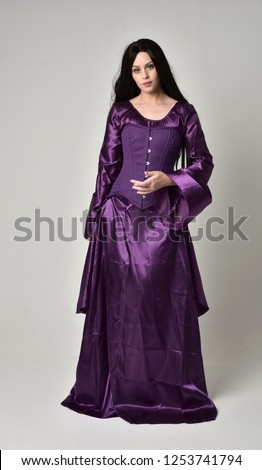 Stock Photo  full length portrait of beautiful girl with long black hair,   wearing purple fantasy medieval gown. standing pose on grey studio background.