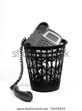 full wastepaper with crumpled papers and old-fashion phone on white background