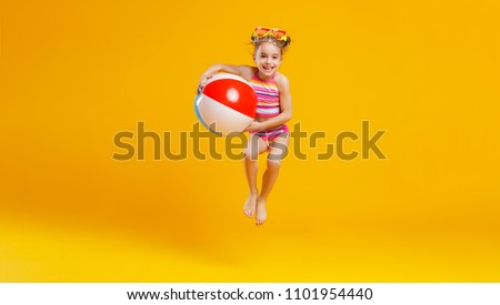 funny happy child   jumping in swimsuit and swimming glasses on colored background