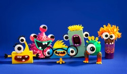 Funny monsters from paper and plasticine on a blue background. Easy creative crafts for children.