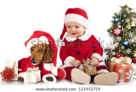 funny small baby in Santa Claus and dog dachshund