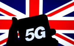 5G letters on a silhouette of a smartphone in the hand with the blurred United Kingdom flag on the background. Authentic photo, not a montage or illustration.