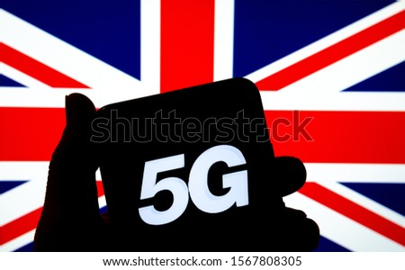 5G letters on a silhouette of a smartphone in the hand with the blurred United Kingdom flag on the background. Authentic photo, not a montage or illustration.  #1567808305