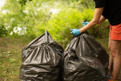 Garbage bags. Big full black garbage bags. Cleaning in nature. Garbage collection for yourself. Earth Day. Saturday clean-up. Nature day