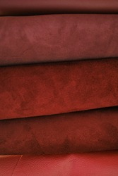 Genuine leather texture.Red  leather and suede in rolls .Leatherworking. Genuine leather red background.Manufacturing from genuine leather.Hobby and craft material