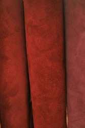 Genuine leather texture.Red  leather and suede in rolls set.Leatherworking. Genuine leather red background.Manufacturing from genuine leather.Hobby and craft material