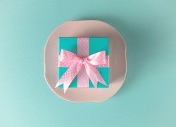 Gift box with a bow, a pink plate on a turquoise background.Minimalism concept, the Fashion style. Top view, flat style.