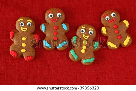 Gingerbread men on red background - stock photo