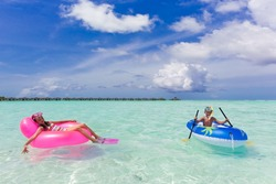 Girl and boy swimming in the clear waters of the tropical ocean. Maldive Islands.